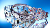 Krásné stříbrné náramky na modrém pozadí — Stock fotografie