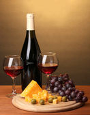 Bottle of great wine with wineglasses and cheese on wooden table on brown background — Stock Photo
