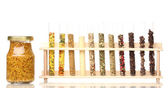 Various spices in tubes and bottle of mustard isolated on white — Stock Photo