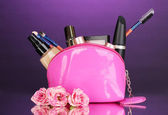 Make up bag with cosmetics and brushes on violet background — Stock Photo