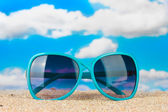 Elegant women's sunglasses at the beach — Stock Photo