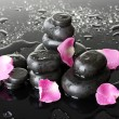 Spa stones with drops and rose petals on grey background — Stock Photo