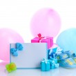Beautiful gifts, baby's bootees, blank postcard, dummy and balloons isolated on white — Stock Photo