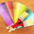 Paint brushes and bright palette of colors on wooden background — ストック写真