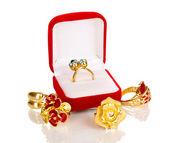 Gouden ring met blauw, zwart, lila en duidelijke kristallen in rode fluwelen doos en vier gouden ringen geïsoleerd op wit — Stockfoto
