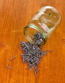 金属の爪と木製の背景にガラスの瓶 — ストック写真