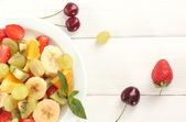 Fresh fruits salad on plate and berries on white wooden table — Stock Photo