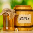 Sweet honey in barrel and jar with flowers on wooden table on green background — Stock Photo