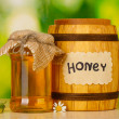 Sweet honey in barrel and jar with flowers on wooden table on green background — Stock Photo #11280629