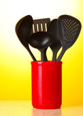 Black kitchen utensils in red cup on yellow background — Stock Photo