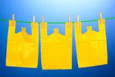 Sacos celofane pendurado na corda em fundo azul — Foto Stock