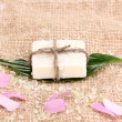 Hand-made herbal soap on sackcloth - Stock Photo