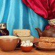 Royalty-Free Stock Photo: Teapot with cup and saucers with oriental sweets - sherbet, halva and turkish delight on wooden table on a background of curtain close-up
