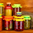 Jars with canned vegetables and fruit on wooden background close-up — Stock Photo #11315415