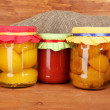 Jars with canned fruit on wooden background close-up — Stock Photo