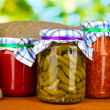 Jars with canned vegetables on green background close-up - Stock Photo