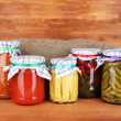 Jars with canned vegetables on wooden background close-up — Stock Photo #11315430