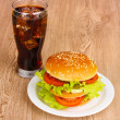 Big and tasty hamburger on plate with cola on wooden table - Stock Photo