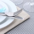 Stock Photo: White empty plates, fork and knife tied with a ribbon and glasses on a grey tablecloth