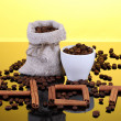Composition of canvas sack and the cup with coffee beans on bright background. Hot. — Stock Photo #11319316