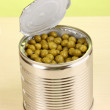 Open tin can of peas on wooden table on green background — Stock Photo