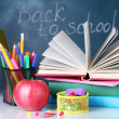 Composition of books, stationery and an apple on the teacher's desk in the background of the blackboard. Back to school. — Stock Photo #11319433
