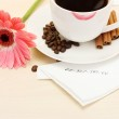 Cup of coffee with lipstick mark and gerbera beans, cinnamon sticks on wooden table — Stock Photo #11319450