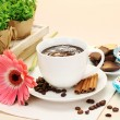 Cup of coffee and gerbera beans, cinnamon sticks on wooden table — Stock Photo
