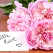 Pink peony with card on wooden background — Stock Photo