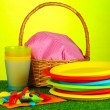 Bright plastic disposable tableware and picnic basket on the lawn on colorful background — Stock Photo #11319973