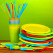 Bright plastic disposable tableware on wooden table on colorful background - Zdjęcie stockowe