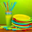 Bright plastic disposable tableware on wooden table on colorful background - Stock Photo