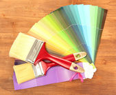 Paint brushes and bright palette of colors on wooden background — Stock Photo