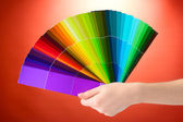 Hand holding bright palette of colors on red background — Stock Photo