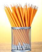 在黄色背景上的木桌上的金属杯中铅铅笔 — 图库照片