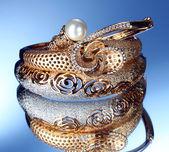Lindas pulseiras de ouro sobre fundo azul — Foto Stock