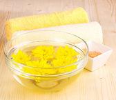 Ciotola con fiori gialli, spa impostazione su fondo in legno — Foto Stock