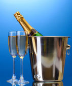 Champagne bottle in bucket with ice and glasses of champagne, on blue background — Stock Photo