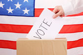 Hand with voting ballot and box on Flag of USA — Stock Photo