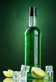 Bottle of absinthe with lime and ice on green background — Stock Photo