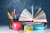 состав книг, канцелярских принадлежностей и яблоко на столе учителя на фоне доске. обратно в школу. — Стоковое фото