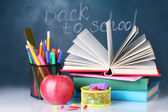 Composition of books, stationery and an apple on the teacher's desk in the background of the blackboard. Back to school. — Foto de Stock