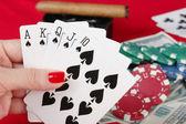 Woman's hand holding playing cards royal flush — ストック写真