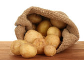 Young potatoes in a sack on a table on white background close-up — Stock Photo