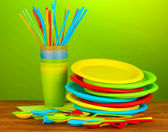 Bright plastic disposable tableware on wooden table on colorful background — Stock fotografie