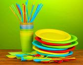 Brilhante utensílios de mesa descartáveis plástico sobre uma mesa de madeira em fundo colorido — Foto Stock