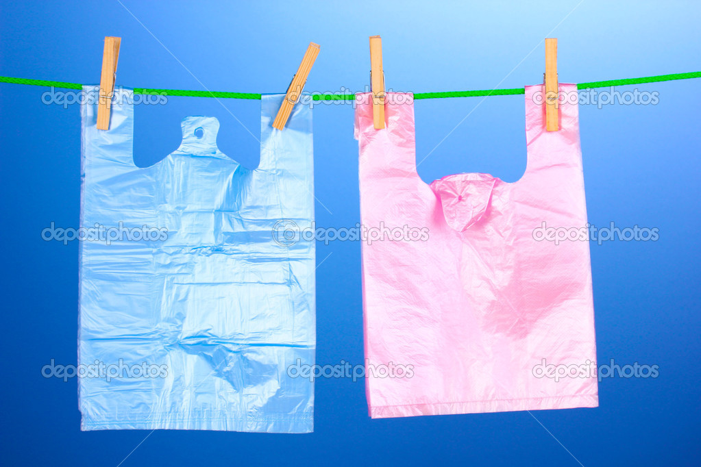 Cellophane bags hanging on rope on blue background — Stock Photo #11314973