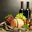 Barrel, bottles and glasses of wine, cheese and ripe grapes on wooden table on grey background — Stock Photo