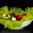 Tasty greek salad isolated on black — Stock Photo