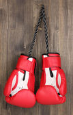 Red boxing gloves hanging on wooden background — Stock Photo